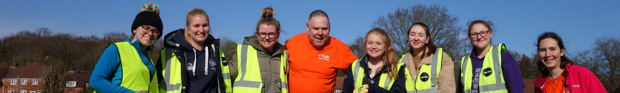 A group of Winchester Hub volunteers in yellow vests are smiling at the camera. In the centre is a councilman in an orange Winchester Hub shirt.