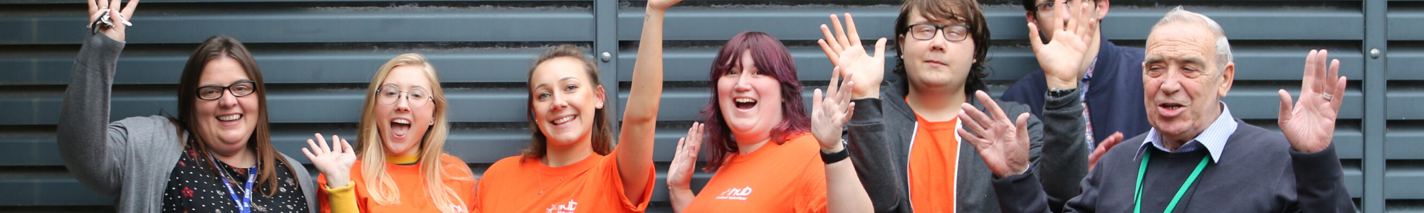 Seven people (four volunteers in orange tops and three members of staff) are smiling at the camera and lifting their hands in the air. They are in front of a background of horizontal grey bars.