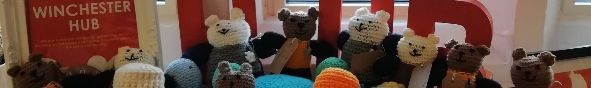 """A group of knitted teddy bears to be donated to the police. To the left is a frame with the white text """"WINCHESTER HUB"""" inside."""